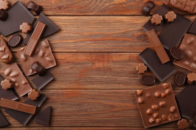 色付きの背景にさまざまな種類のチョコレート製品とテキスト用の場所を接写