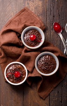 Chocolate pudding in ceramic bowl with cherries