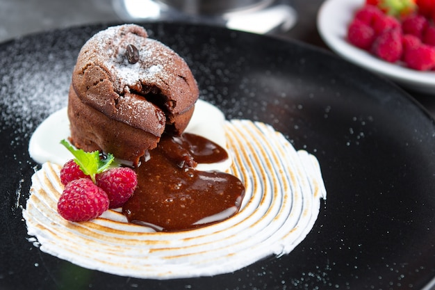 Chocolate pudding lava cake with vanilla cream, raspberry and mint on a black plate