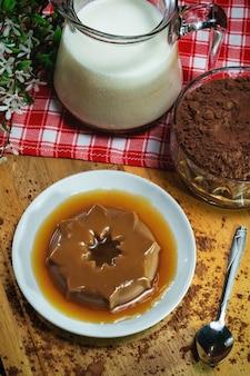 Шоколадный пудинг на фарфоровой тарелке. молочная банка и стеклянная банка с шоколадом в по. деревянная основа с тканью в шахматном порядке. черный фон.