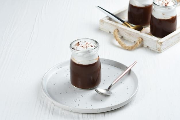 ホイップクリームとチョコレートをポーショングラスにトッピングしたチョコレートプディング