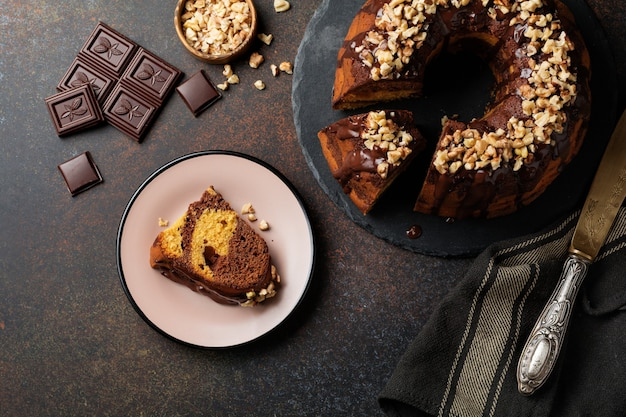 Chocolate and pumpkin bundt cake with chocolate glaze and walnut on dark concrete background.