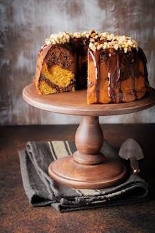 Chocolate and pumpkin bundt cake with chocolate glaze and walnut on dark concrete background