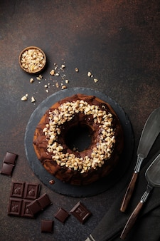 Chocolate and pumpkin bundt cake with chocolate glaze and walnut on dark concrete surface. selective focus. top view. copy space