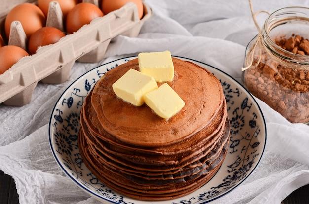 上の明るい背景にバターとチョコレートのパンクケーキ。家庭料理、素朴なスタイル。