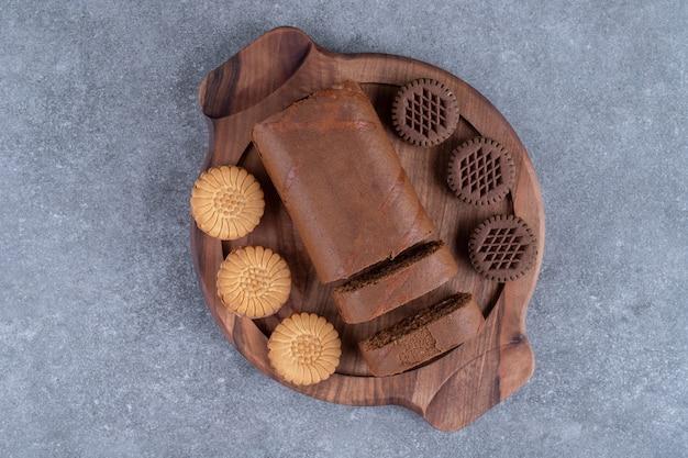 木の板にチョコレートロールケーキとビスケット