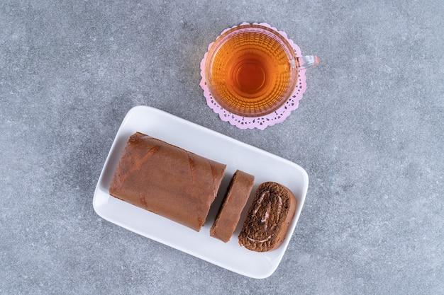 대리석 표면에 초콜릿 롤 케이크와 차 한잔
