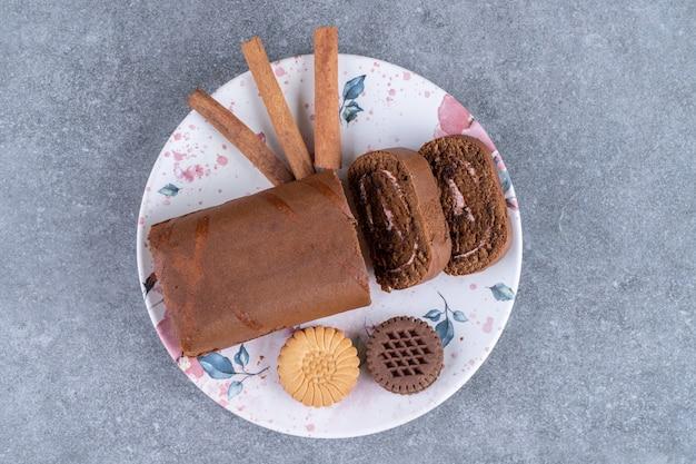 다채로운 접시에 초콜릿 롤 케이크, 비스킷, 계피 스틱