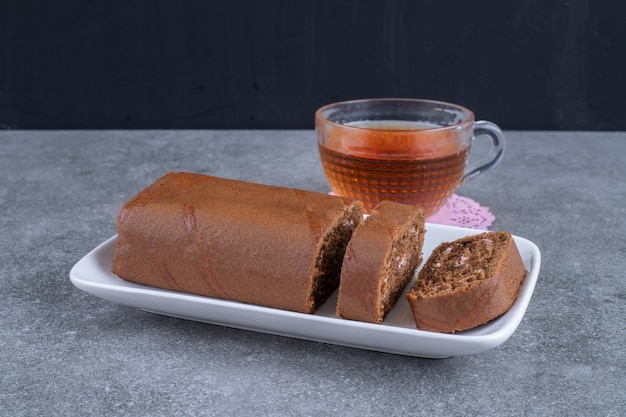 Chocolate roll cake and cup of tea on marble surface