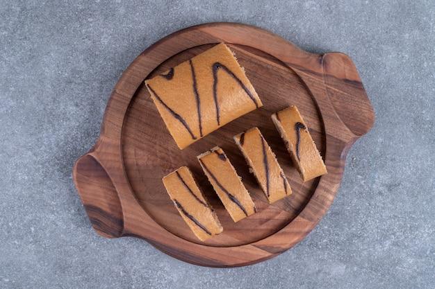 Шоколадный рулет на деревянной тарелке