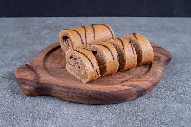 Rotolo di torta al cioccolato su piatto di legno
