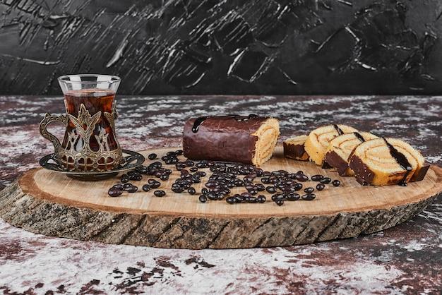 木の板に飲み物とチョコレートロールケーキ。