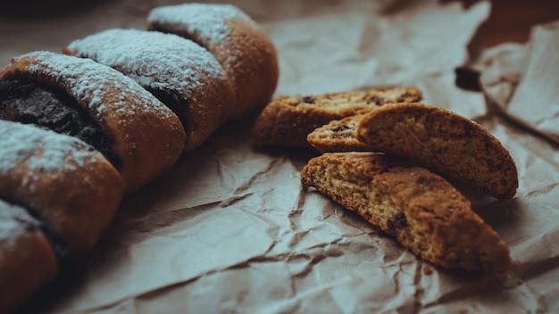 Шоколадные рулетики с аппетитной начинкой и вкуснейшими сухариками, посыпанные сахарной пудрой. на фоне крафт-бумаги коричневого цвета