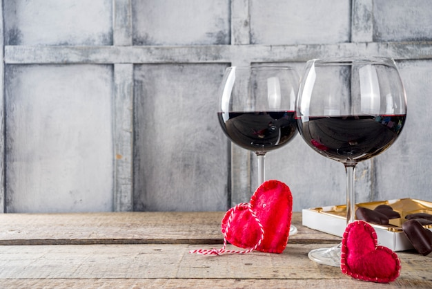 Chocolate, roses, wine glasses and heart box on wooden table