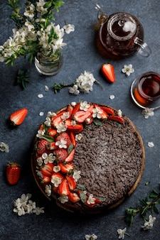 Chocolate round cake with strawberry on dark background. tasty chocolate grated pie