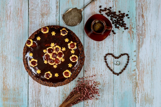 Chocolate rum cake with coffee and ring on wooden table