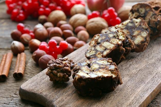 木製の背景の上のまな板にチョコレートサラミ、クローズアップ