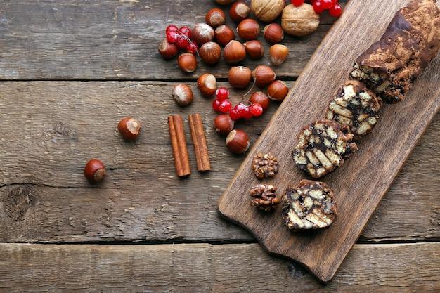 木製の背景の上のまな板にチョコレートサラミ