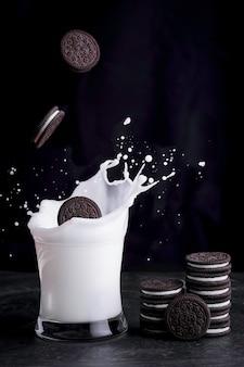 Шоколадное печенье-сэндвич со сладко-сливочной начинкой, упавшее в брызги свежего молока в стакане