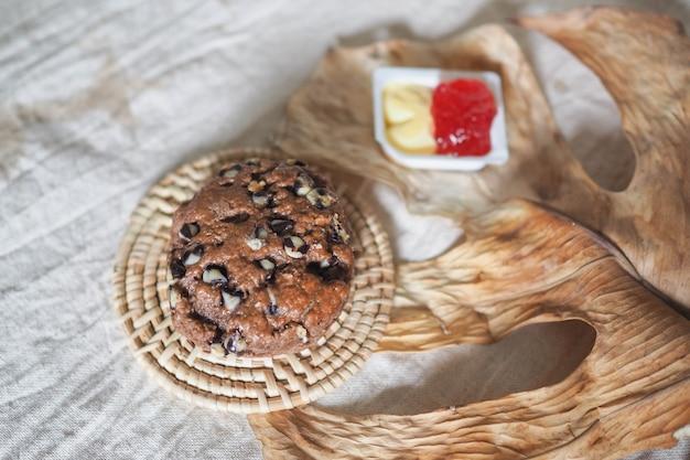 いちごジャムと生地の表面に乾燥した葉を持つクロテッドクリームのチョコレートスコーン