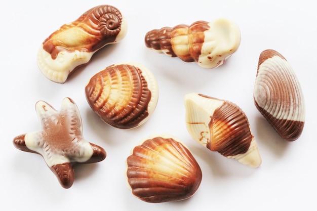 Шоколадные ракушки еда фоном, изолированные на белом фоне