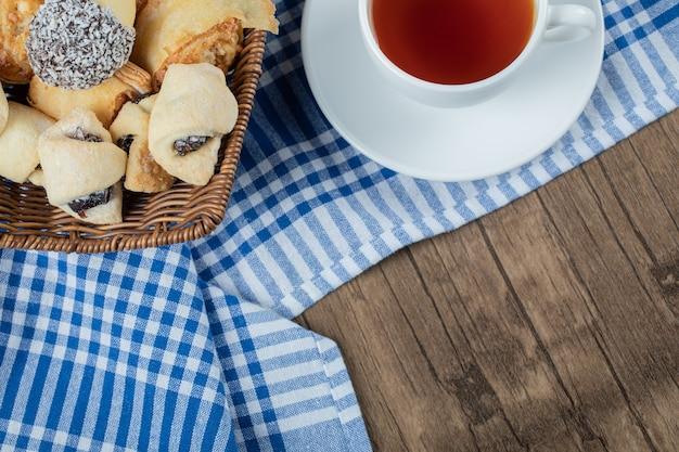 Biscotti al cioccolato al sesamo in un cesto di legno con una tazza di tè earl grey.