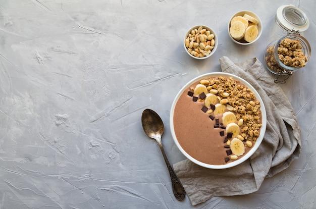 ライトグレーのコンクリートの背景にバナナ、グラノーラ、ピーナッツのチョコレートスムージーボウル。ヘルシーなベジタリアン朝食。テキスト用のスペースがある上面図。