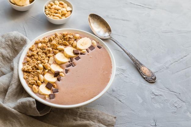 Шоколадный коктейль с бананами, мюсли и арахисом на светло-сером бетонном фоне. здоровый вегетарианский завтрак.