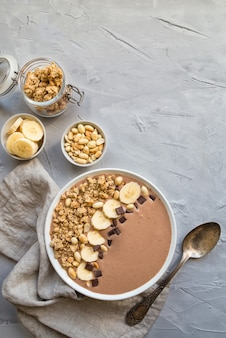 Chocolate smoothie bowl with bananas, granola and peanuts on light gray concrete.
