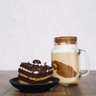 Chocolate smoothie in jar with slice of cake on wooden table