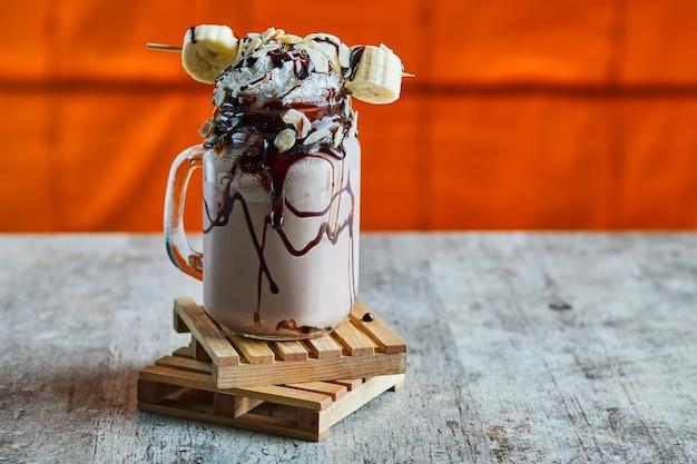 明るい表面の木板にチョコシロップ、バナナ、ホイップクリームを添えたチョコレートスムージー