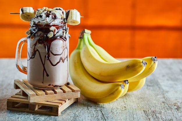 Frullato al cioccolato con sciroppo di cioccolato e ramo di banane