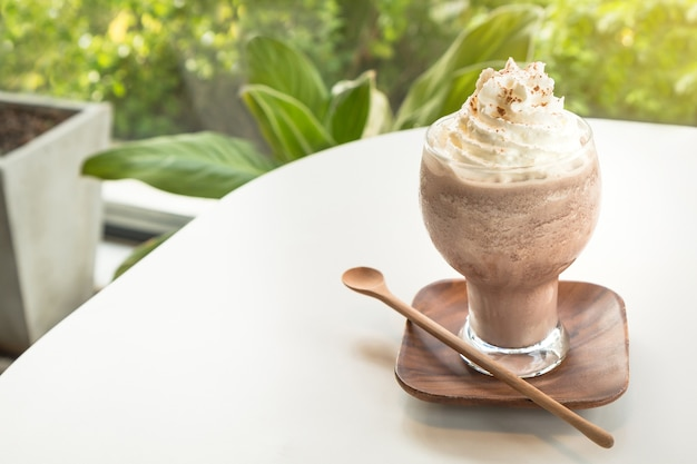 Chocolate smoothies topped with whipped cream and cocoa powder.