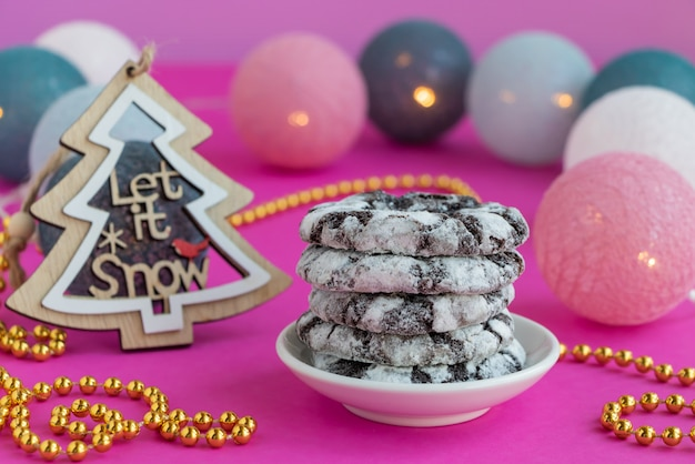 Chocolate snowy cookies on a pink background