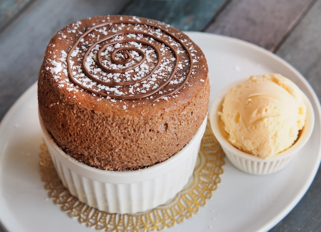 Chocolate souffle with vanilla ice cream on white plate . french traditional dessert.