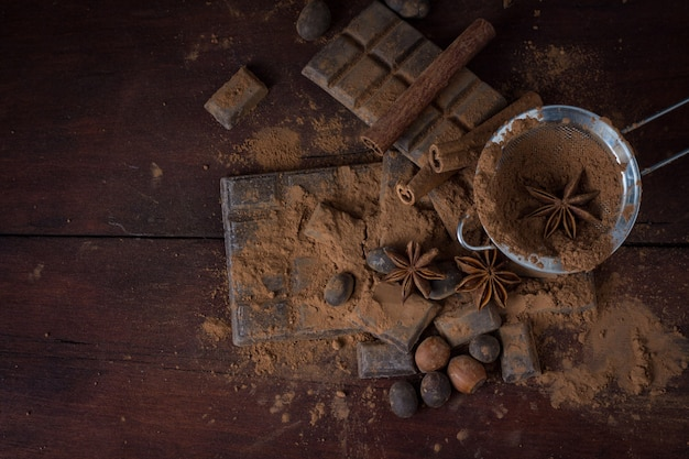 Chocolate, spices, spoon with cocoa, metal strainer, hazelnut on dark wooden surface. copy space. flat lay, top view