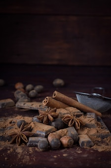 Chocolate, spices, spoon with cocoa, metal strainer, hazelnut on dark wooden surface. copy space