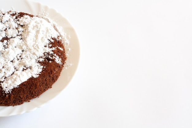 Chocolate sponge cake with powdered sugar on a plate, copy space