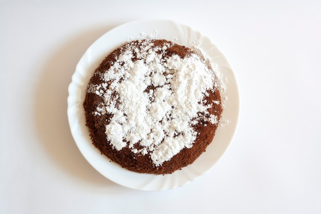 Chocolate sponge cake with powdered sugar on a plate, isolated
