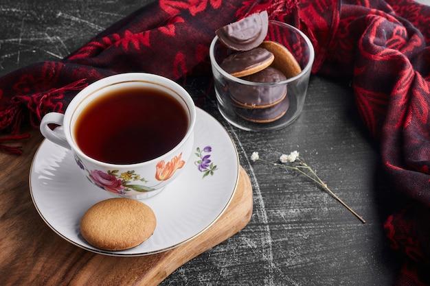 お茶とガラスのカップにチョコレートスポンジクッキー。