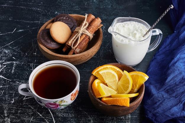 カード、お茶、オレンジと木製のカップにチョコレートスポンジクッキー。