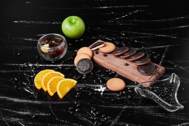 Biscotti di spugna al cioccolato su una tavola di legno con tisana.