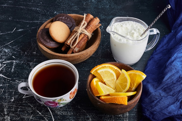 Chocolate sponge cookies in a wooden cup with curd, tea and orange.