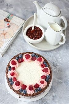 Chocolate sponge creamy cake with berries and coconut flakes