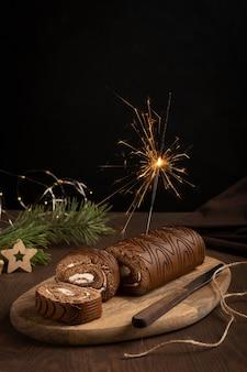 Шоколадный бисквитный рулет со сливками с фейерверком на деревянном столе на черном фоне