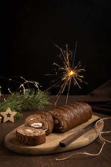 Chocolate sponge roll with cream with firework sparkler on wooden table against black