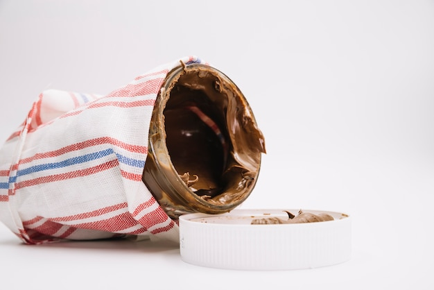 Chocolate spread jar wrapped in napkin with open lid on white background