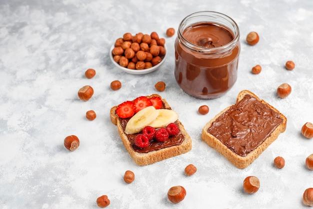 コンクリート、copyspaceのガラスの瓶にヘーゼルナッツとチョコレートスプレッドまたはヌガークリーム