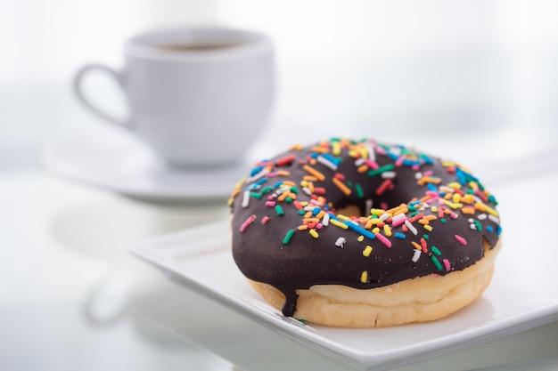 Шоколад брызгает пончик на белом фоне и чашку кофе на свет.