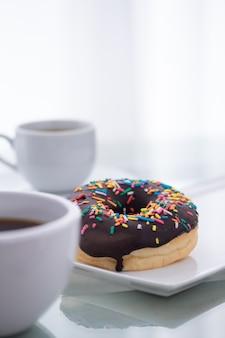 Шоколад брызгает пончик на белой тарелке и чашку кофе